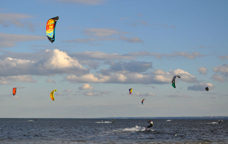 Man kiteboarding on sea against sky