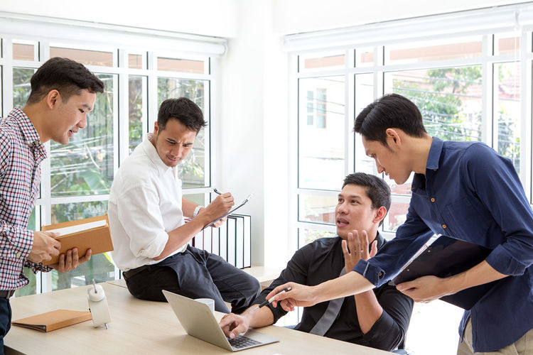 Business colleagues discussing over laptop while working in office