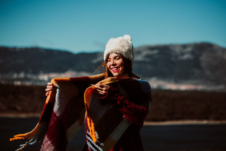 Smiling young woman standing against sky during winter