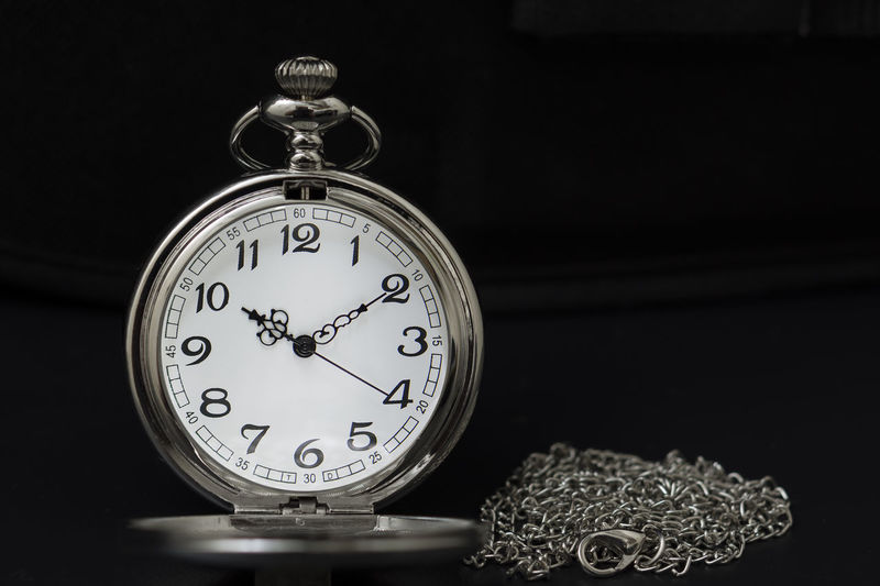 Close-up of pocket watch against black background