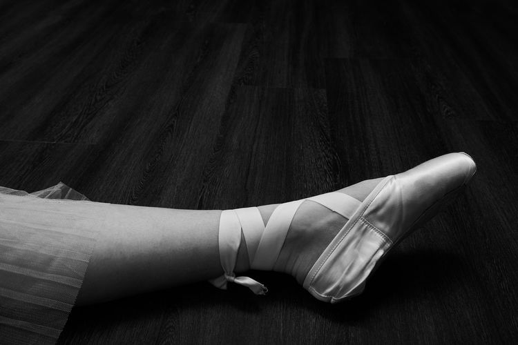 Low section of woman wearing shoes on wooden floor
