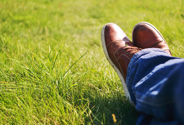 Having a break Adult Break Casual Clothing Day Grass Green Human Body Part Human Leg Jeans Leisure Activity Lifestyles Low Section One Person Outdoors Pause People Real People Relaxation Shoe Urban