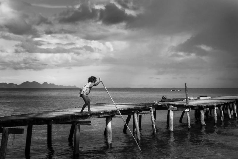 Man standing on pier over sea against sky