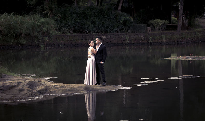 Pre Nup Beauty In Nature Bonding Bride Bridegroom Full Length Lake Lifestyles Love Nature Outdoors Real People Standing Togetherness Two People Water Wedding Wedding Dress Young Women