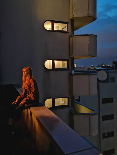 Woman standing by window in illuminated building