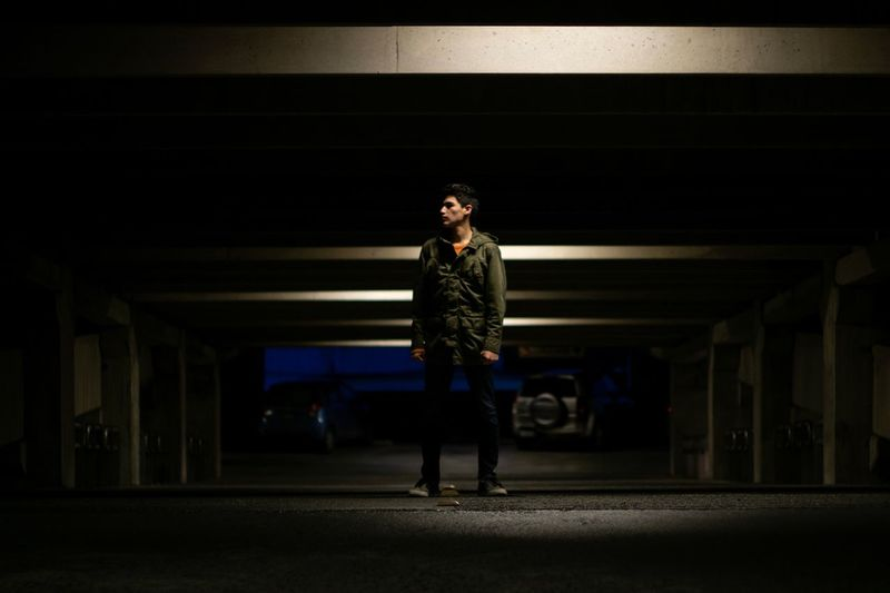 Full length of young man standing in parking lot at night