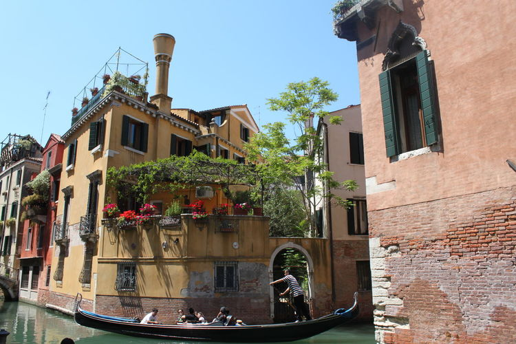 Gondolier sailing gondola in grand canal against old buildings