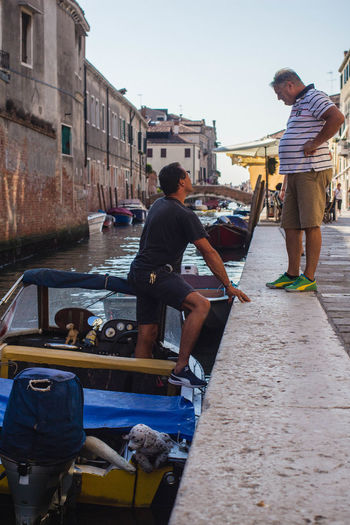 Everyday Lives Romantic Architecture Boat Canal Canals And Waterways Casual Clothing Chatting City On Water Day Italy Men Motorboat Nautical Vessel Outdoors Urban Life Venice Venice Life Water