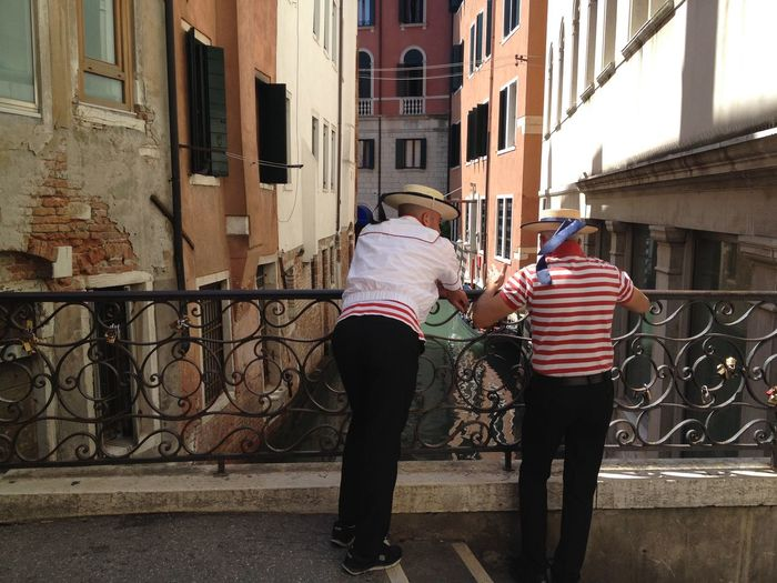 Rear view of two women walking in front of buildings