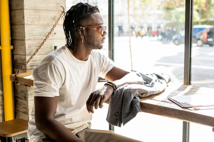 Young man looking at camera while sitting on window