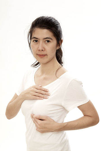 Portrait of woman with hands on chest standing against white background