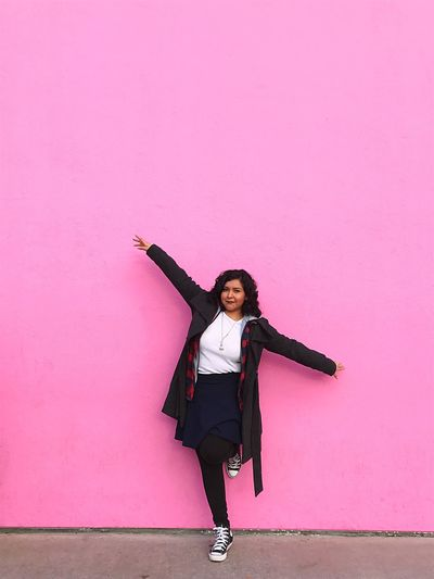 Full Length Of Young Woman With Arms Outstretched Against Pink Wall