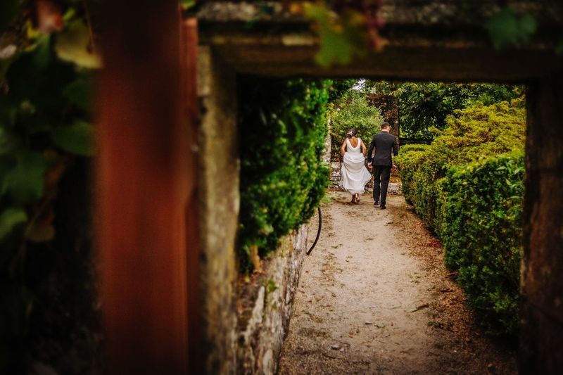 Rear View Of Wedding Couple Walking On Footpath In Park