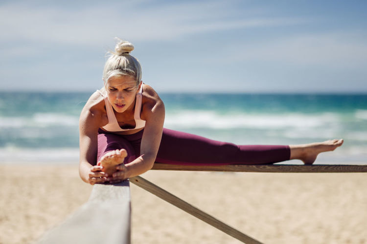 Caucasian woman practicing yoga at seashore. Young female stretching legs in the beach in Cadiz, Andalusia, Spain. Sea Blond Hair One Person Women Beach Hair Land Water Day Leisure Activity Lifestyles Holiday Trip Nature Vacations Sport Sky Adult Horizon Over Water Outdoors Hairstyle