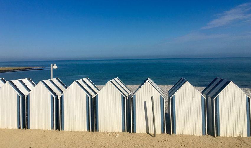 Beach huts in row against blue sky
