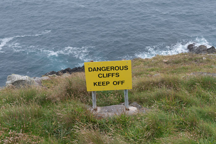 Beach Beauty In Nature Communication Danger Day Grass High Angle View Horizon Over Water Ireland Nature No People Outdoors Safety Sea Text Tranquility Warning Warning Sign Water Wave Yellow
