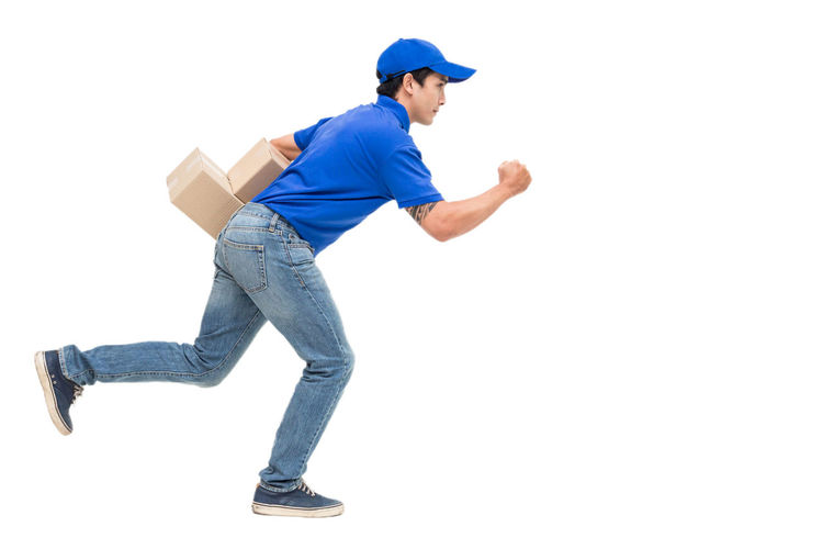 Deliveryman holding cardboard box isolated on white background Box Delivery Blue Casual Clothing Copy Space Cut Out Full Length Hat Indoors  Jeans Leg Leisure Activity Lifestyles Looking Men One Person Side View Standing Studio Shot White Background Young Adult Young Women