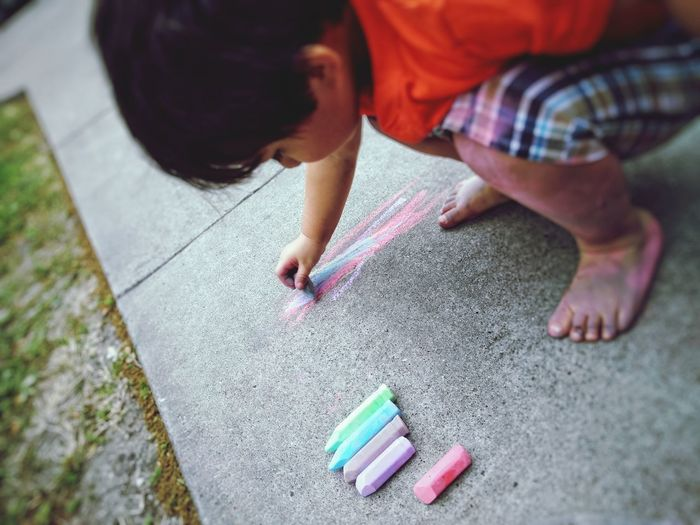High Angle View Of Boy Writing With Chalk On Footpath