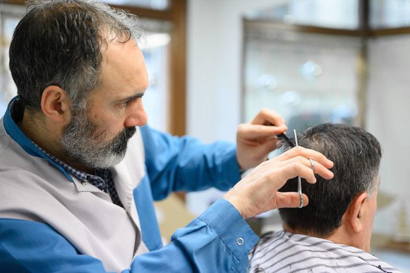 Hairdresser cutting customer hair