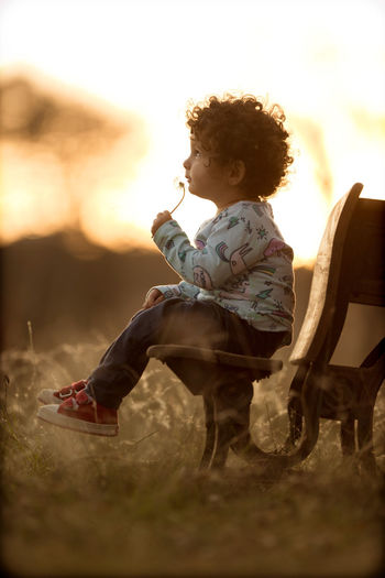 Boy sitting on field against sky during sunset