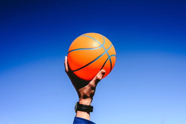 Cropped hand holding basketball against blue sky