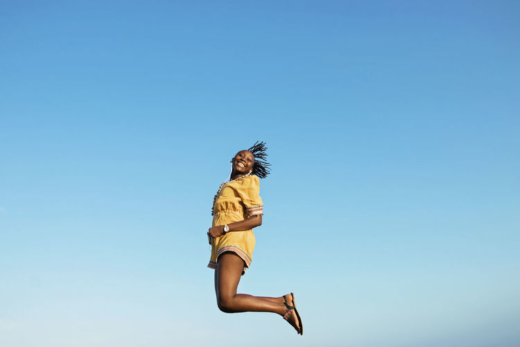 Low angle portrait of cheerful woman jumping against clear blue sky