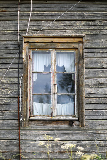 Low angle view of window of abandoned building