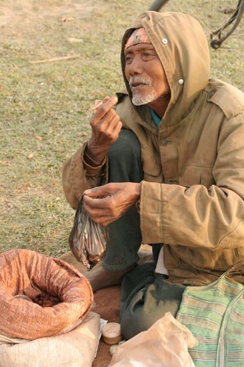 Senior Vendor Selling Food While Sitting On Grassy Field