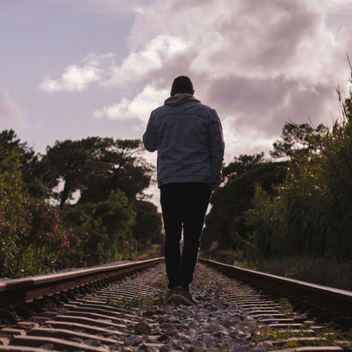 Rear view of man standing on railroad tracks against sky
