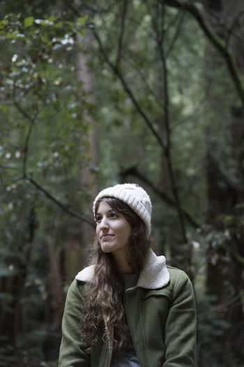 Woman against trees at forest