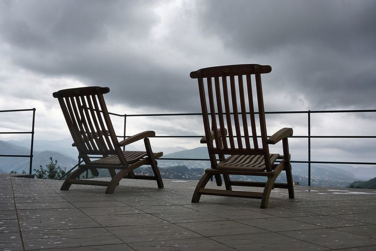 Wooden Deck Chairs Against Cloudy Sky