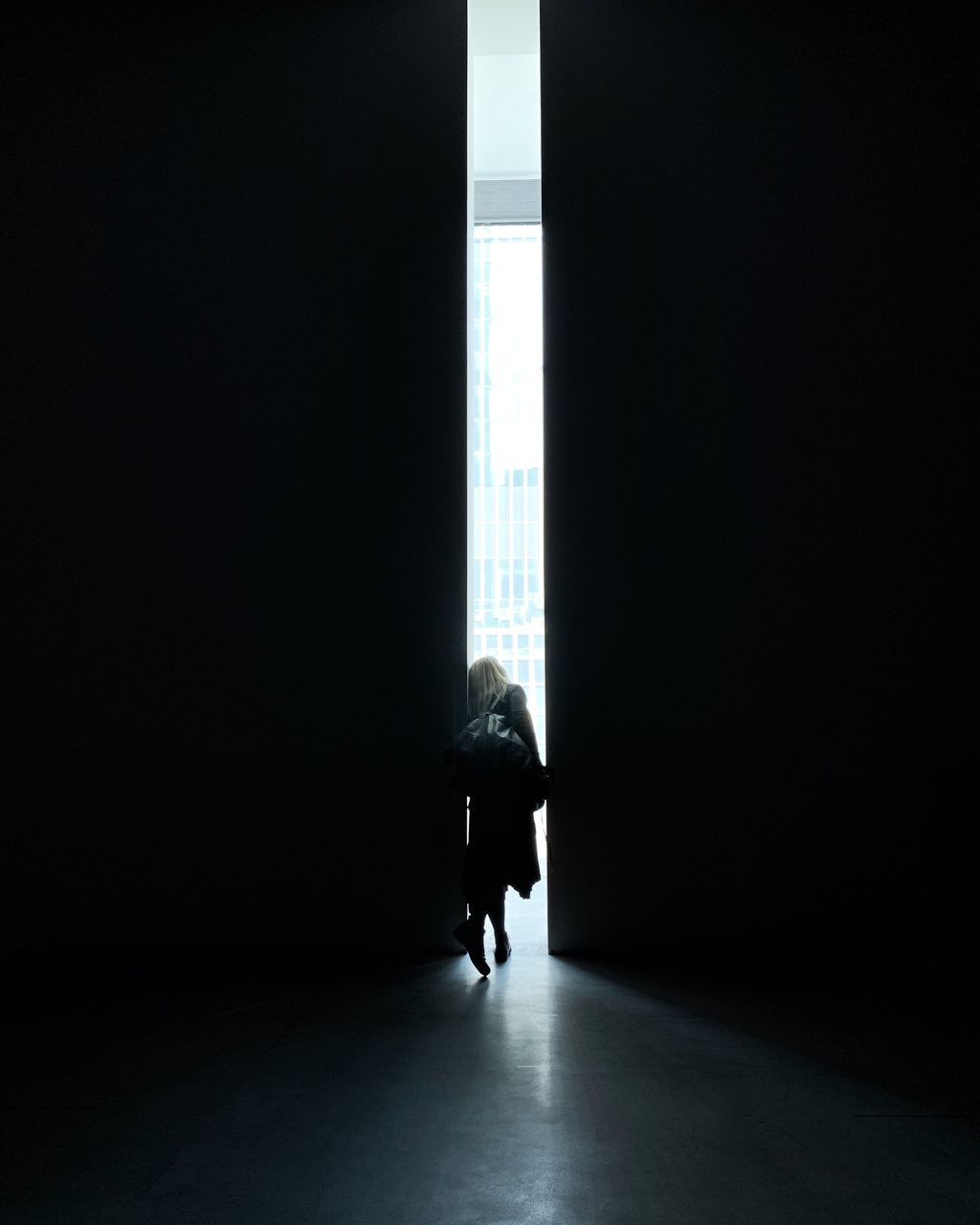one person, indoors, real people, full length, copy space, lifestyles, architecture, day, men, dark, built structure, leisure activity, rear view, walking, silhouette, window, women, flooring, sunlight, light at the end of the tunnel