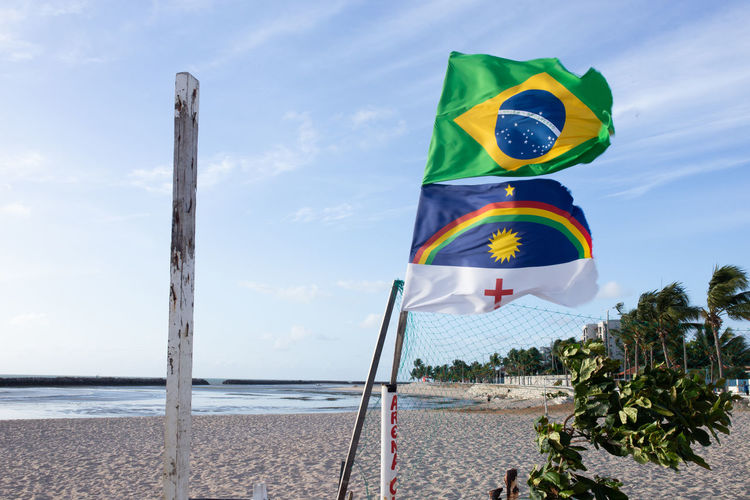 Multi colored flags at beach against sky