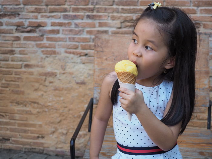 Cute girl holding ice cream outdoors