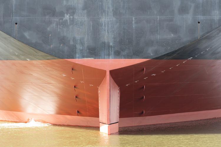 Sailboat sailing on sea by wall