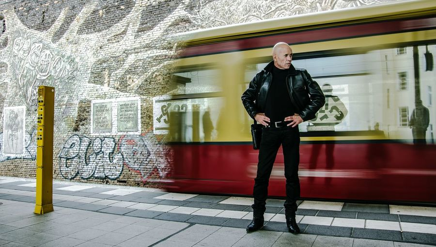 Man Standing With Hands On Hip Against Blurred Motion Of Tramway