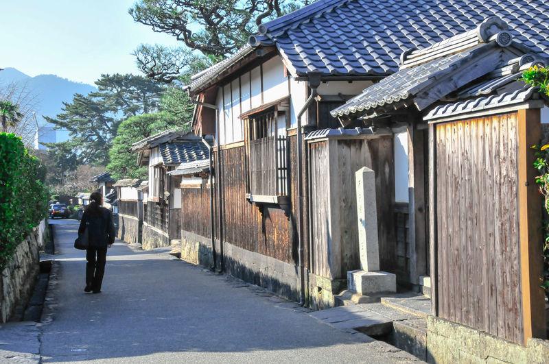 Man walking on street against house