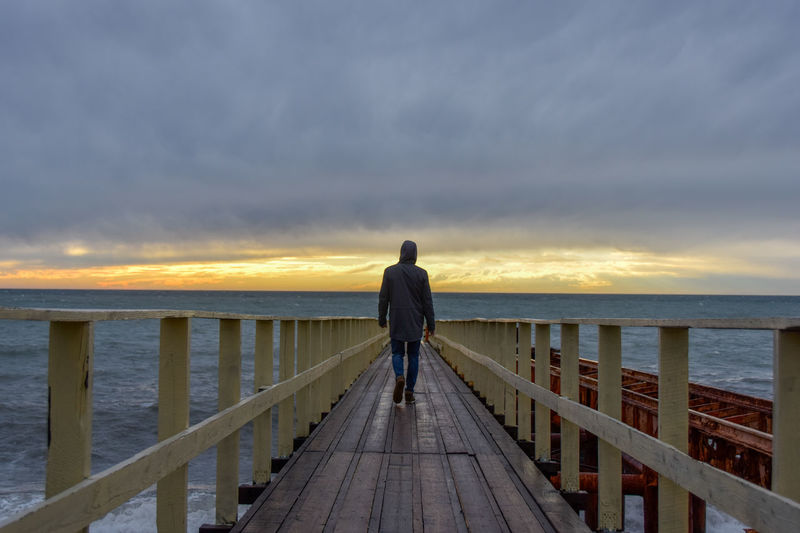 Rear view of man standing on railing against sea during sunset