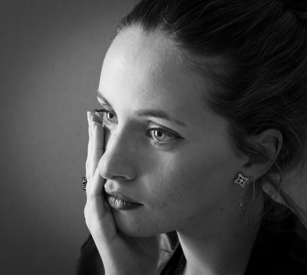 Young woman looking away against gray background