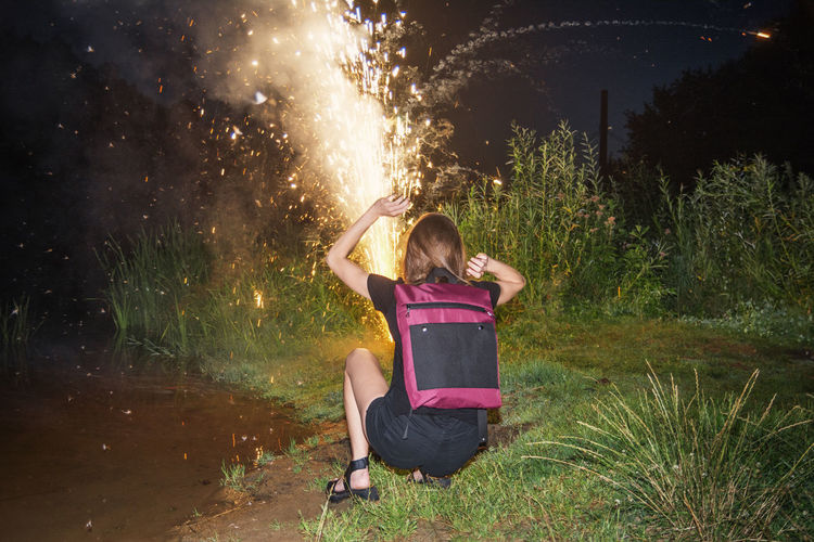 Full Length Of Woman Crouching By Burning Firework On Field At Night