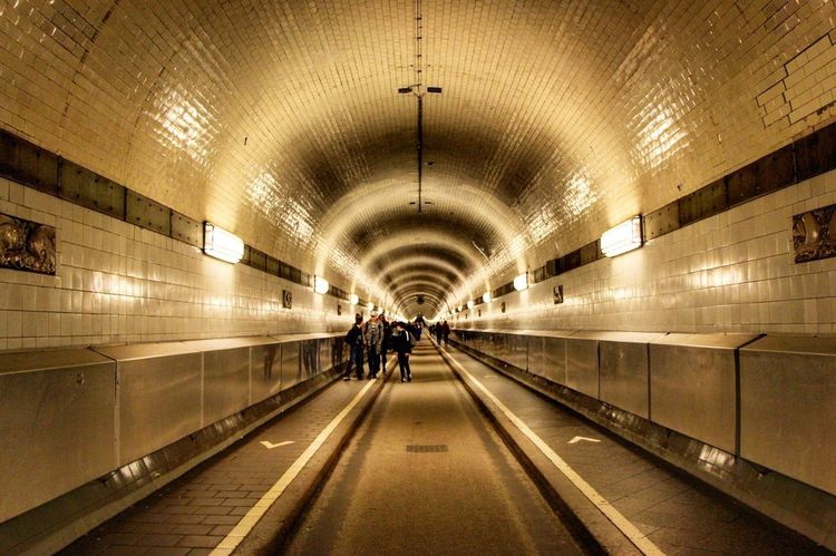 The Secret Spaces Illuminated Built Structure Architecture The Way Forward Real People Ceiling Indoors  Lighting Equipment Rear View Long Walking Underpass Arch One Person Men Full Length Tunnel Futuristic Day People