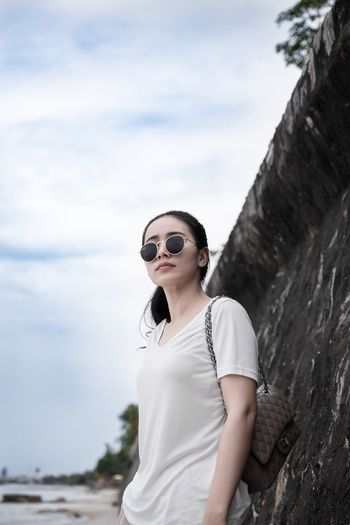 Young woman wearing sunglasses while standing by stone wall at beach