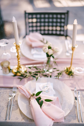 Hand holding glass of flower on table in restaurant