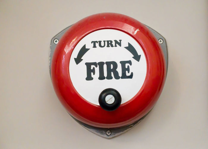 an old-fashioned, hand-cranked fire alarm. Man Retro Alarm Circle Close-up Crank Fire Bell Low Tech Low Technology Manually Cranked Metal No People Old Old Fashion Red Safety Text Turn