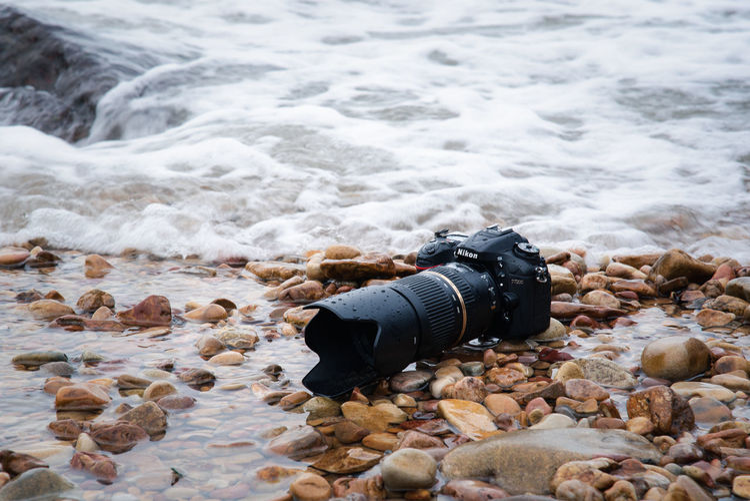 High angle view of camera on rock at sea shore