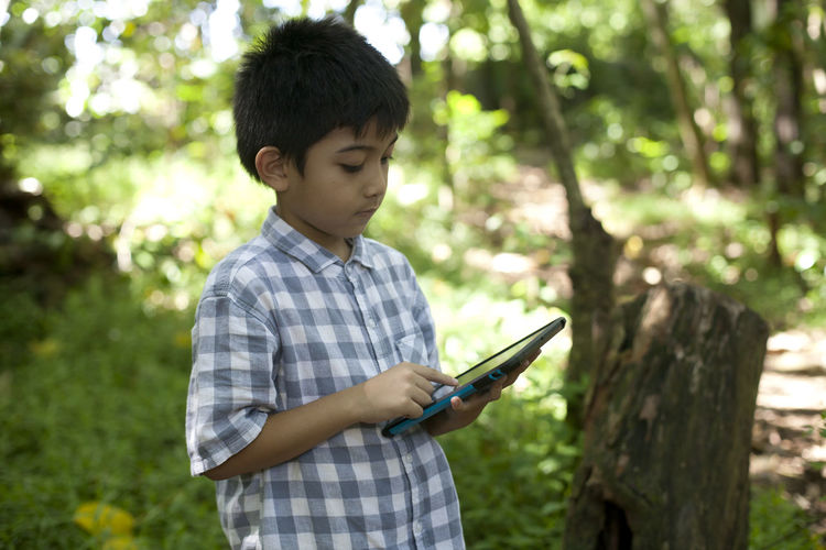 Boy Using Digital Tablet At Yard