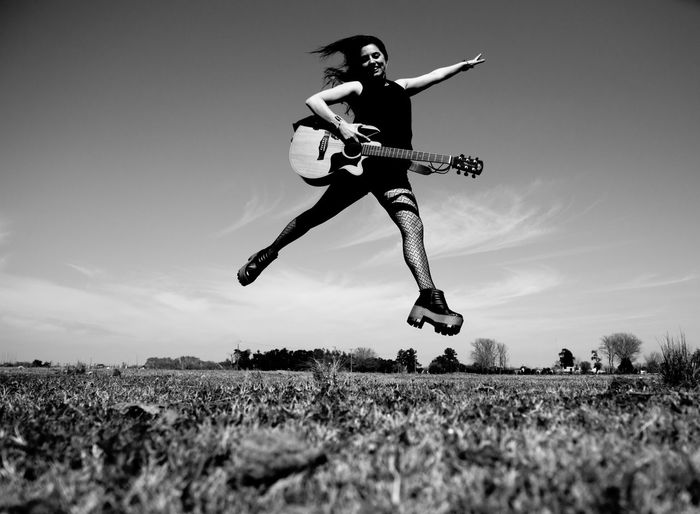 Low angle view of man jumping on field against sky