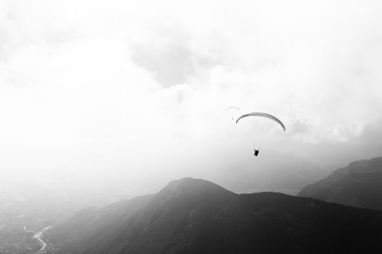 Person paragliding over mountain against cloudy sky