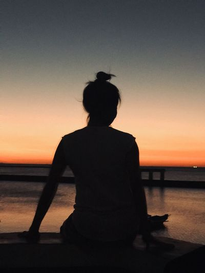 Rear view of silhouette woman looking at sea against clear sky during sunset