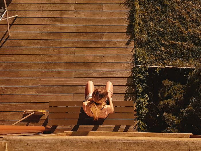 High angle view of woman sitting on bench